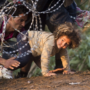 Refugees clamber through barbed wire as they cross from Serbia to Hungary, in Roszke, Thursday, Aug. 27, 2015. Over 10,000 migrants, including many women with babies and small children, have crossed into Serbia over the past few days and headed toward Hungary. (AP Photo/Darko Bandic)/XDB103/234691918525/1508270926